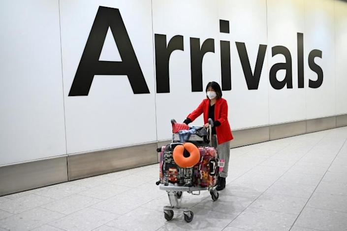 Face masks are being used as a frontline defense in China and around the world against the deadly coronavirus -- here, a passenger is seen arriving at London's Heathrow airport (AFP Photo/DANIEL LEAL-OLIVAS)