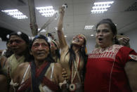 Waoranis leader Nemonte Nenquimo, center, and lawyer Lina Espinosa, right, celebrate after a judged ruled in their favor in a lawsuit filed against the Ministry of Non-Renewable Natural Resources for opening up oil concessions on their ancestral land, in Puyo, Ecuador, Friday, April 26, 2019. (AP Photo/Dolores Ochoa)