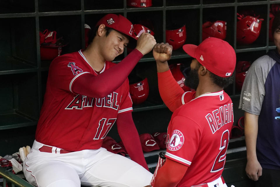 Los Angeles Angels designated hitter Shohei Ohtani, left, is greeted by Luis Rengifo prior to a baseball game against the Seattle Mariners Saturday, Sept. 25, 2021, in Anaheim, Calif. (AP Photo/Mark J. Terrill)