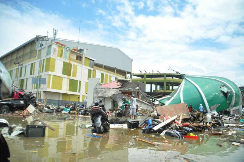 People survey the damage following a massive earthquake and tsunami in Palu, Central Sulawesi, Indonesia, Sunday, Sept. 30, 2018. Rescuers were scrambling Sunday to try to find trapped victims in collapsed buildings where voices could be heard screaming for help after a massive earthquake in Indonesia spawned a deadly tsunami two days ago. (AP Photo/Rifki)