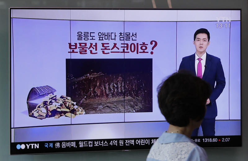 "A woman walks by a TV screen showing the news program reporting about a sunken Russian warship at the Seoul Railway Station in Seoul, South Korea, Thursday, July 19, 2018. A South Korean company's claim to have found a sunken Russian warship has triggered investor frenzy amid unconfirmed rumors that the ship was carrying 200 tons of gold when it sank in 1905. The part of letters read ""Sunken Treasure Ship Donskoi ?"" (AP Photo/Lee Jin-man)"
