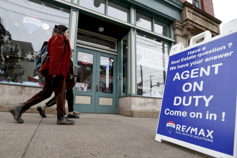 FILE- In this Jan. 4, 2019, file photo people walk by a real estate office in Pittsburgh's Lawrenceville neighborhood. Buying a home for the first time is challenging no matter your marital status. But doing so in an unmarried partnership poses unique challenges. (AP Photo/Keith Srakocic, File)