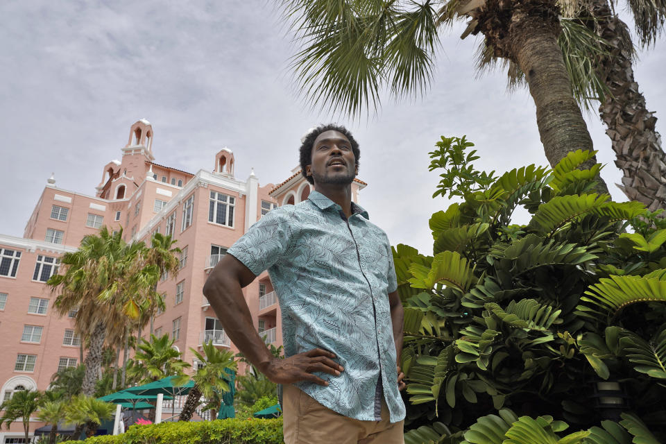 """Jared Wofford poses for photos outside of the Don Cesar hotel Thursday, June 17, 2021, in St. Petersburg, Fla. Wofford portrays a bartender at the hotel in the Amazon series """"Life's Rewards,"""" an original, scripted TV series commissioned by travel marketers in St. Petersburg and Clearwater, Florida, seeking to draw quarantine-weary tourists to the area's sugar sand beaches. (AP Photo/Chris O'Meara)"""