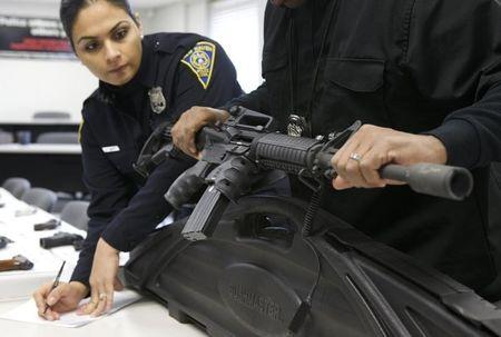 A New Haven police officer catalogues a Bushmaster semi-automatic assault rifle that is turned in during a gun buyback event in New Haven