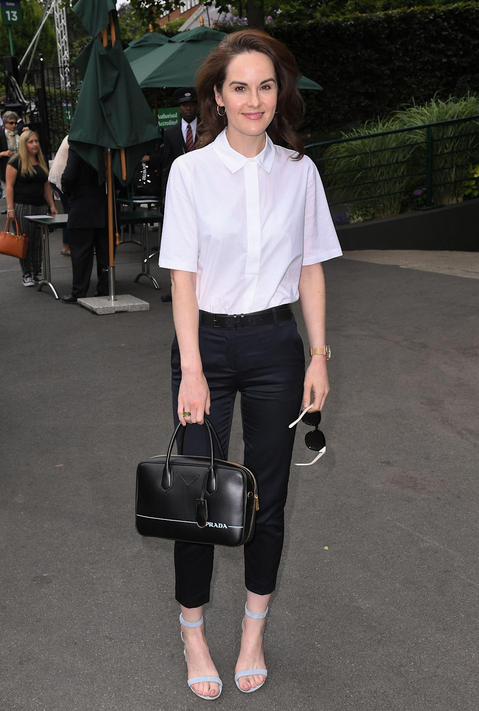 <p>Actress Michelle Dockery opted for a smart monochrome get-up thanks to a crisp boxy shirt and tailored trousers. <em>[Photo: Rex]</em> </p>