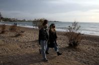 People wearing protective face masks walk on a beach during an unusual warm day, amid the coronavirus disease (COVID-19) pandemic, in the southern suburb of Faliro in Athens