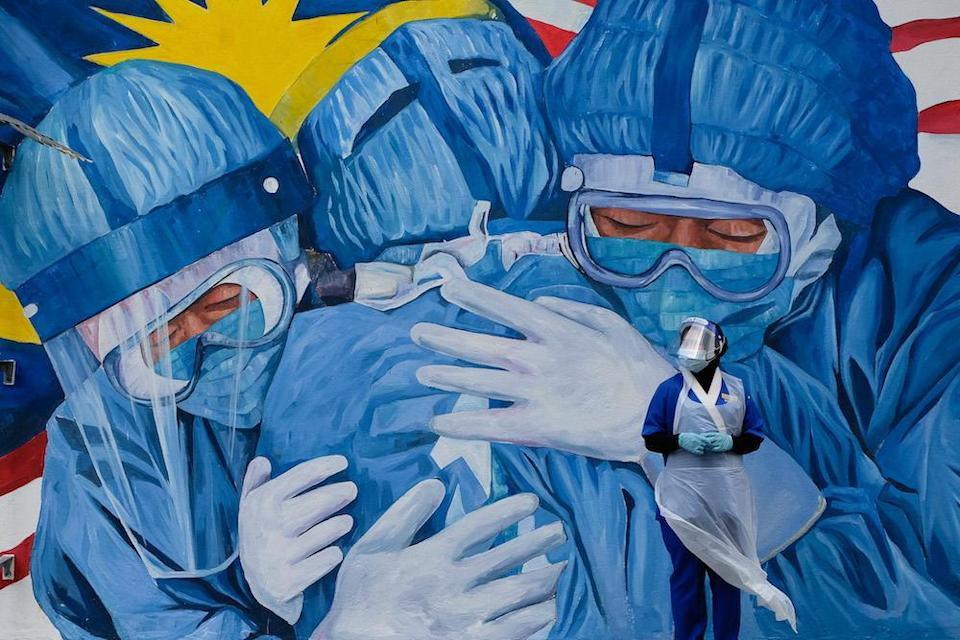 A medical worker wearing personal protective equipment takes a breather in front of a mural featuring frontliners outside a clinic in Shah Alam December 6, 2020. — Picture by Yusof Mat Isa