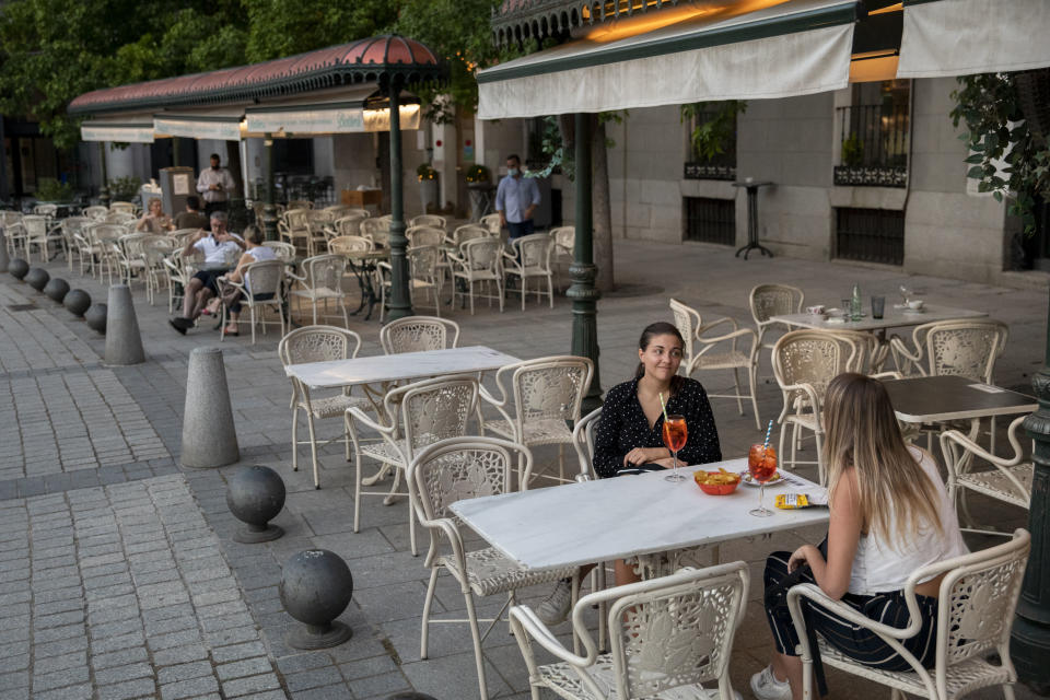 Women sit at the terrace of a restaurant at Opera Square in Madrid