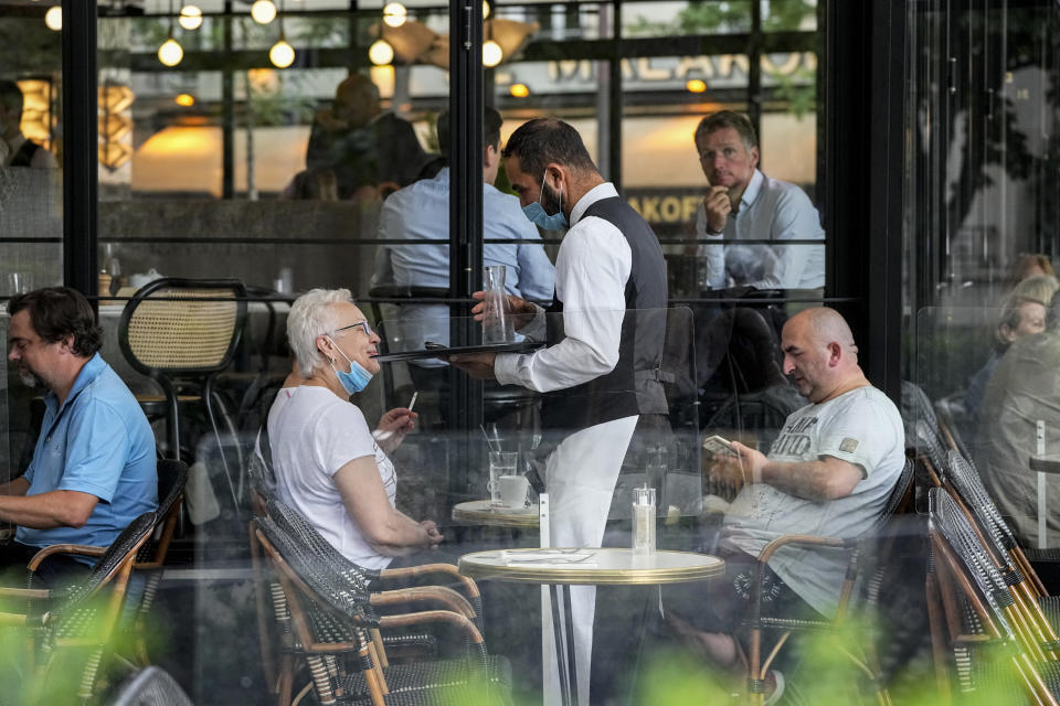 A waiter wearing a face mask to protect against coronavirus serves at a restaurant terrace in Paris, Monday, July 26, 2021. France's parliament approved a law requiring special virus passes for all restaurants and domestic travel, and mandating vaccinations for all health workers. (AP Photo/Michel Euler)