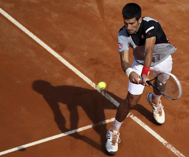 Serbia's Novak Djokovic returns a backhand during his semifinal match against Canada's Milos Raonic at the Italian open tennis tournament in Rome, Saturday, May 17, 2014. Djokovic won the match and advanced to the final. (AP Photo/Gregorio Borgia)