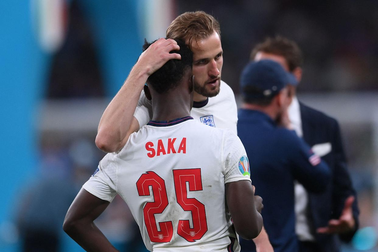 England captain Harry Kane consoles teenage midfielder Bukayo Saka after their loss in the UEFA Euro 2020 final football match to Italy at the Wembley Stadium in London on Sunday. Photo: Laurence Griffiths/Pool/ AFP via Getty