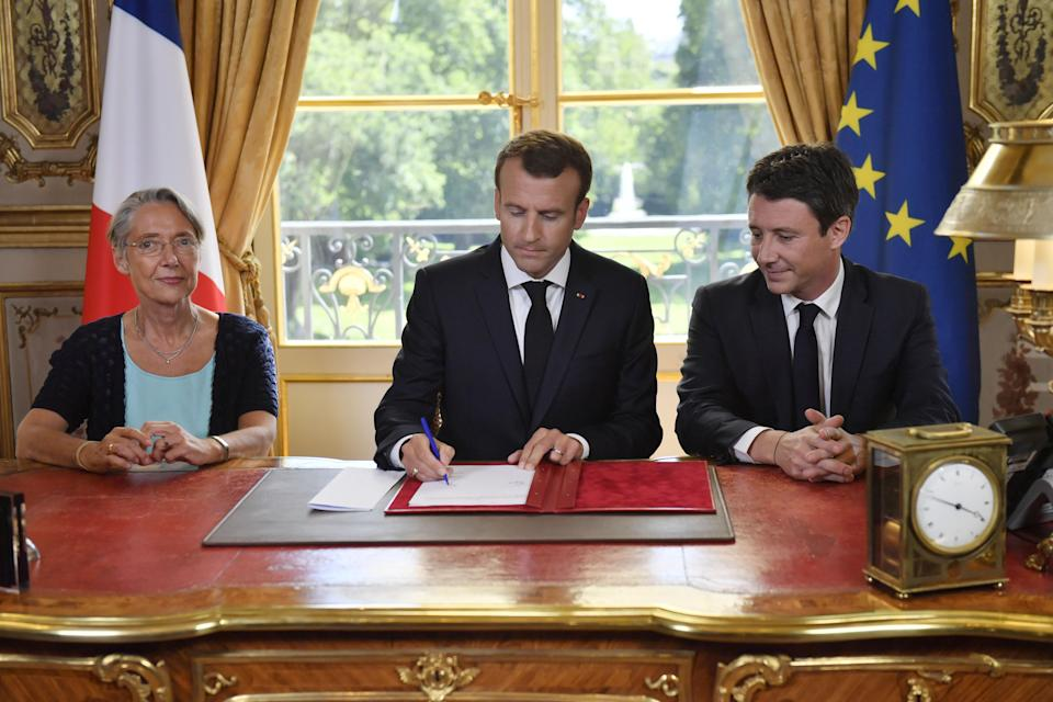 French President Emmanuel Macron (C), flanked by French Transports Minister Elisabeth Borne (L) and French government spokesman Benjamin Griveaux, signs the controversial rail reform, at the Elysee Palace in Paris, on June 27, 2018. / AFP PHOTO / POOL / JULIEN DE ROSA