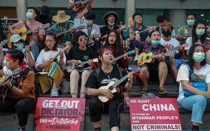 An anti-coup protester flashes the three-fingered salute as others play instruments and sing in Yangon, Myanmar - AP