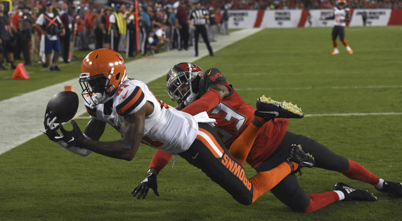 Cleveland Browns wide receiver Rashard Higgins (81) can't hang onto the ball after getting past Tampa Bay Buccaneers cornerback Carlton Davis (33) during the first half of an NFL preseason football game Friday, Aug. 23, 2019, in Tampa, Fla. (AP Photo/Jason Behnken)