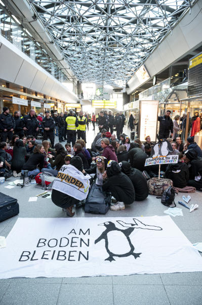 Climate activists block the entrance hall of the Tegel airport in Berlin, Germany, Sunday, Nov. 10, 2019.A banner reads 'stay on the ground'.  (Fabian Sommer/dpa via AP)
