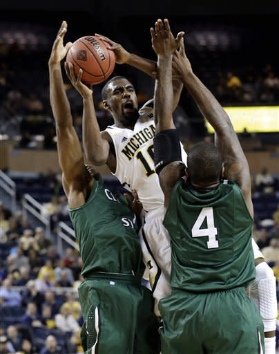 Michigan guard Tim Hardaway Jr., center, drives between Cleveland State guard Sebastian Douglas, left, and center Devon Long (4) during the first half of their NCAA college basketball game in the second-round of the NIT Season Tip-Off tournament at Crisler Arena in Ann Arbor, Mich., Tuesday, Nov. 13, 2012. (AP Photo/Paul Sancya)