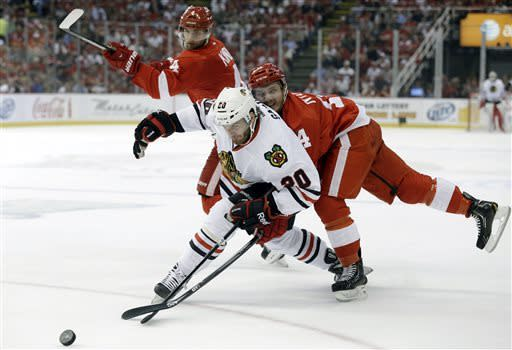 Detroit Red Wings center Gustav Nyquist (14), of Sweden, wraps up Chicago Blackhawks left wing Brandon Saad (20) as defenseman Jakub Kindl (4), of the Czech Republic, watches during the first period of an NHL hockey Stanley Cup playoffs Western Conference semifinal game in Detroit, Monday, May 20, 2013. (AP Photo/Paul Sancya)