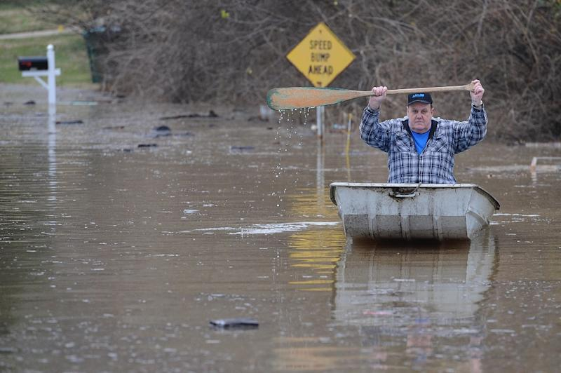 A resident canoes himself down a street submerged in floodwater from the Meramec River in Arnold, Missouri on December 30, 2015 (AFP Photo/Michael B. Thomas)