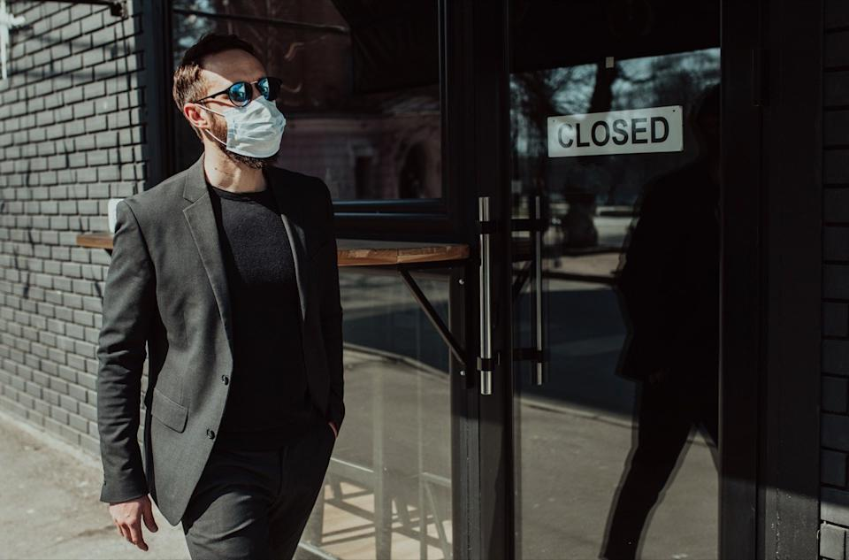 Handsome man with beard in trendy formal suit wearing a medical face mask