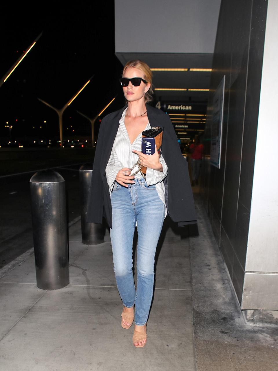 <p>Rosie HW is a professional at airport dressing, and for a recent flight to LA the modle nailed off-duty in a pair of blue skinnies, a white shirt and shoulder-draped blazer. <em>[Photo: Getty]</em> </p>