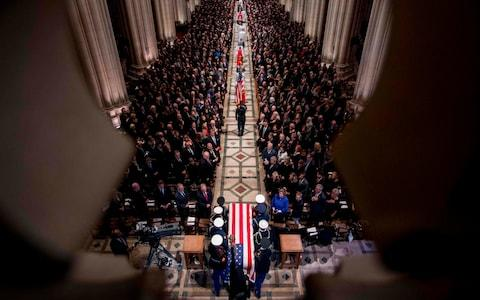 The flag-draped casket of former US President George H W Bush arrives carried by a military honor guard during a State Funeral at the National Cathedral  - Credit: ANDREW HARNIK/AFP