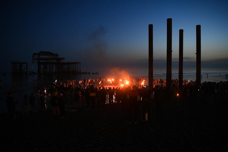 BRIGHTON, UNITED KINGDOM - MARCH 30: Fire jugglers draw a crowd on Brighton beach on March 30, 2021 in Brighton, United Kingdom.  (Photo by Mike Hewitt/Getty Images)