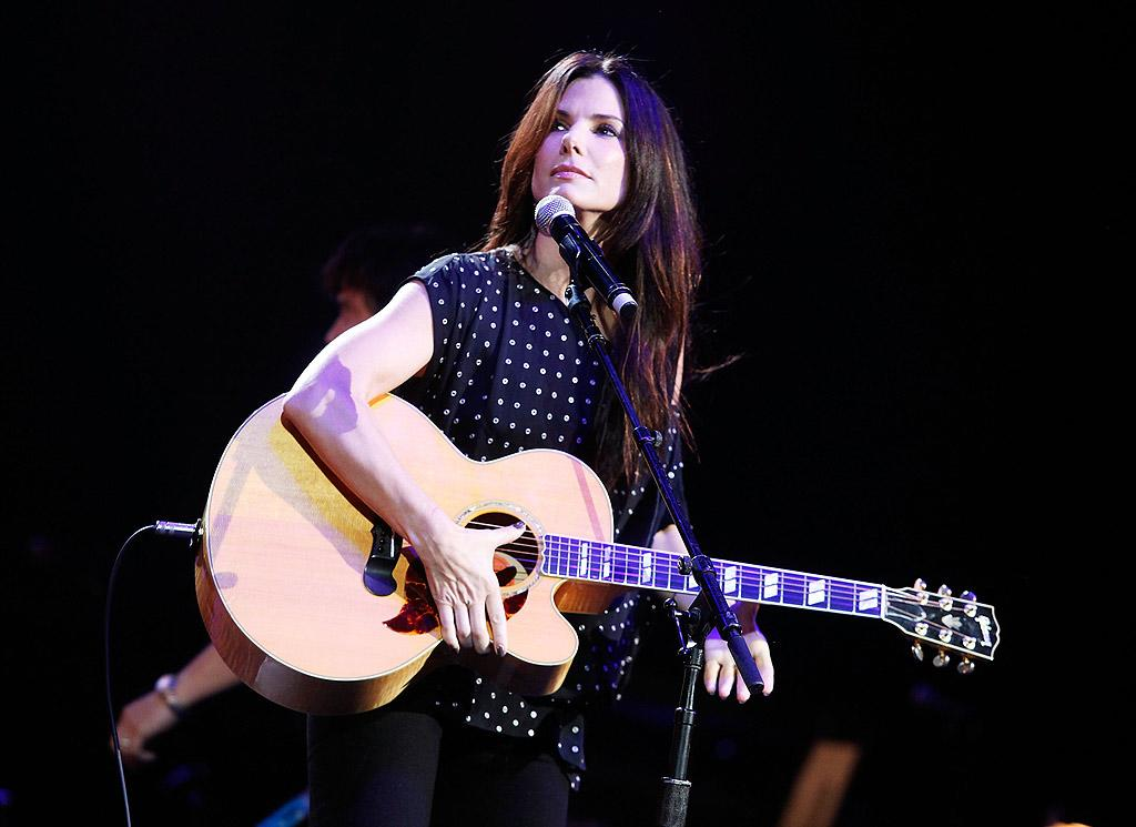 "Sandra Bullock surprised the crowd at Nashville Rising: A Benefit Concert for Flood Recovery Tuesday night when she hit the stage and attempted to play Deep Purple's ""Smoke on the Water."" The Oscar winner cut her performance short and laughed, """"OK, who am I kidding? I can't play for crap!"" before introducing Faith Hill. Ed Rode/Nashville Rising/<a href=""http://www.gettyimages.com/"" target=""new"">GettyImages.com</a> - June 22, 2010"