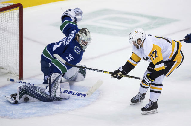 Pittsburgh Penguins' Bryan Rust, right, is stopped by Vancouver Canucks goalie Jacob Markstrom, of Sweden, during the second period of an NHL hockey game, Saturday, Oct. 27, 2018, in Vancouver, British Columbia. (Darryl Dyck/The Canadian Press via AP)