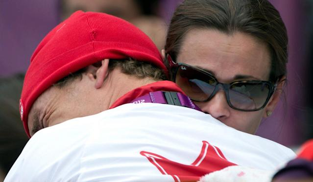 Canada's Simon Whitfield is hugged by his wife after crashing and retreating from the men's triathlon at Hyde Park during the Summer Olympics in London on Tuesday, August 7, 2012. THE CANADIAN PRESS/Sean Kilpatrick