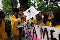Manik Marganamahendra, a student leader at the University of Indonesia, hands out signs as he prepares to takes part in a protest over human rights, corruption and social and environmental issues in Jakarta, Indonesia