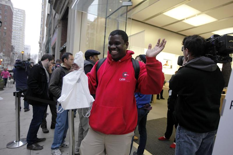 Robert Smith exits an Apple retail store with a new iPad tablet, Friday, March 16, 2012, in Philadelphia. Stores along the East Coast have begun selling Apple's latest tablet computer. It's going on sale at 8 a.m. local time Friday in the U.S. and nine other countries. (AP Photo/Matt Rourke)