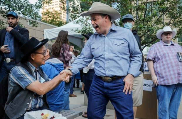 Alberta Premier Jason Kenney, right, greets a supporter at his annual Stampede breakfast in Calgary on July 12. On Sunday, the premier said in social media posts that the Stampede took place 'after the pandemic' — a message health experts are questioning. (Jeff McIntosh/The Canadian Press - image credit)
