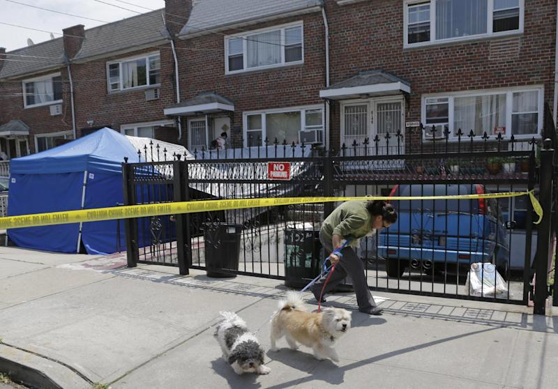"A woman ducks under crime scene tape in front of a New York city house once occupied by a famous gangster, Tuesday, June 18, 2013, in New York. The work started Monday at the home of James Burke, a Lucchese crime family associate known as ""Jimmy the Gent."" He was the inspiration for Robert De Niro's character in the 1990 Martin Scorsese movie ""Goodfellas."" Burke died behind bars in 1996, two decades after authorities say he masterminded a nearly $6 million robbery at New York's Kennedy Airport, one of the largest cash thefts in American history. The Queens house is still owned by the Burke family, but others now live there. (AP Photo/Kathy Willens)"