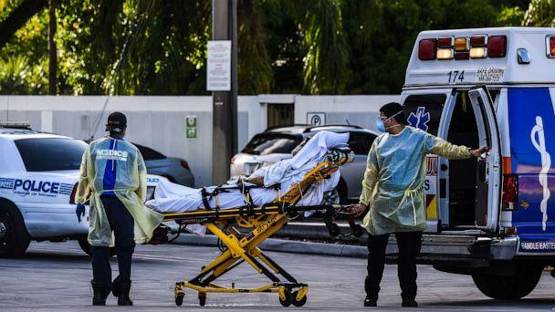 PHOTO: Medics transfer a patient on a stretcher from an ambulance outside of Emergency at Coral Gables Hospital where COVID-19 patients are treated in Coral Gables near Miami, Florida, on July 30, 2020. (Chandan Khanna/AFP via Getty Images)