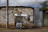 Teacher Gerardo Ixcoy sits parked just outside the doorway of a student's home, inside his secondhand adult tricycle he converted into a mobile classroom, in Santa Cruz del Quiche, Guatemala, Wednesday, July 15, 2020. Ixcoy has installed protective plastic sheets to protect against the new coronavirus transmission, a whiteboard and a small solar panel that powers an audio player he uses for some lessons. (AP Photo/Moises Castillo)