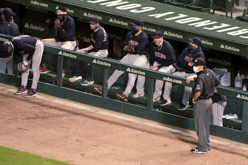 Cleveland Indians wait out a brief suspension of play during the fifth inning after a drone landed in center field, before taking off and flying out of the ballpark during a baseball game between the Chicago Cubs and the Indians on Wednesday, Sept. 16, 2020, in Chicago. (AP Photo/Mark Black)