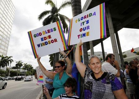 People hold signs at a gay rights rally following the U.S. Supreme Court strike down of the Defense of Marriage Act, in Fort Lauderdale