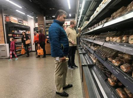 """Customers browse packaged wraps, sandwiches and salads at Amazon's new """"grab-and-go"""" store in Seattle, Washington, U.S., January 18, 2018. Photo taken January 18, 2018. REUTERS/Jeffrey Dastin"""
