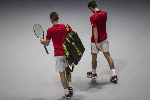 Serbia's Novak Djokovic, right, and teammate Viktor Troicki leave the tennis court after losing the Davis Cup quarterfinal doubles match against Russia's Karen Khachanov, right, and Andrey Rublev in Madrid, Spain, Friday, Nov. 22, 2019. (AP Photo/Bernat Armangue)