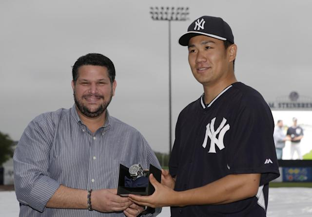Baseball Writers Association of America representative Mark Feinsand, left, poses for a photograph with New York Yankees starting pitcher Masahiro Tanaka after presenting Tanaka with a watch after the Yankees awarded Tanaka with the 2014 James P. Dawson award, given annually to the outstanding Yankee rookie in spring training, before a spring exhibition baseball game in Tampa, Fla., Saturday, March 29, 2014. Saturday's game against the Miami Marlins was was canceled due to rain. (AP Photo/Kathy Willens)
