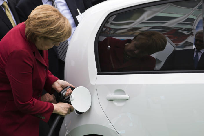 German Chancellor Angela Merkel plugs a charging nozzle into an electric car at the Electric Mobility Conference in Berlin May 27, 2013. Credit: Reuters/Thomas Peter