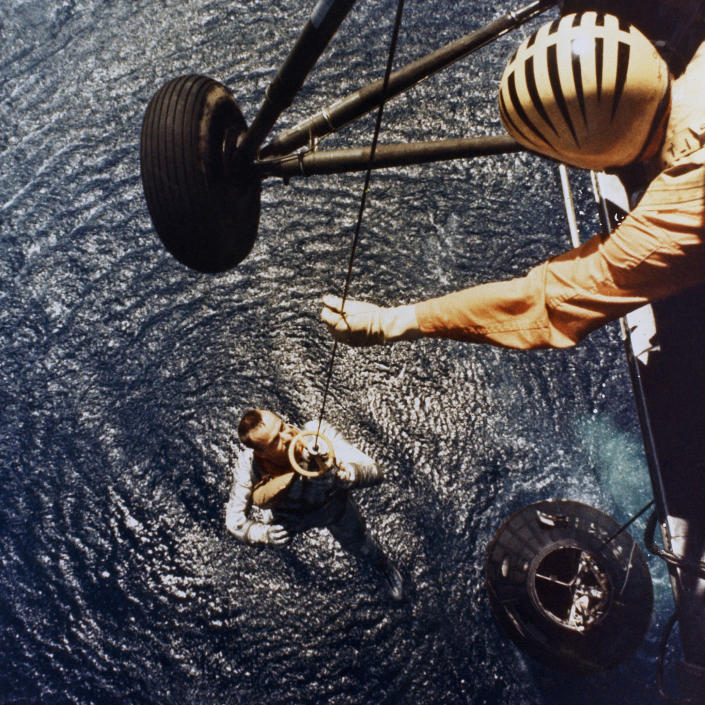 In this May 5, 1961 photo made available by NASA, astronaut Alan Shepard is retrieved by a U.S. Marine helicopter after splashdown in the Atlantic Ocean at the end of his sub-orbital flight down range from the Florida eastern coast. (NASA via AP)