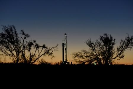 FILE PHOTO: A horizontal drilling rig on a lease owned by Parsley Energy operates at sunrise in the Permian Basin near Midland