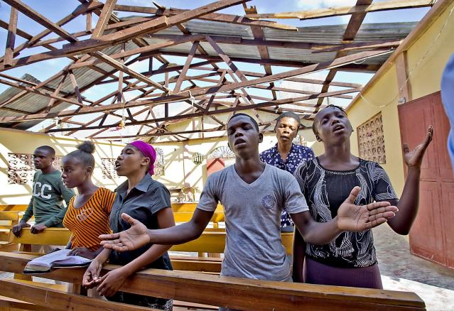 <p>Jimmy Mondesir, middle, worships at L'Elise de Dieu in Morne la Source, Haiti, on Oct. 9, 2016, without it's roof, lost in Hurricane Matthew. (Photo: Patrick Farrell/Miami Herald/TNS via Getty Images) </p>