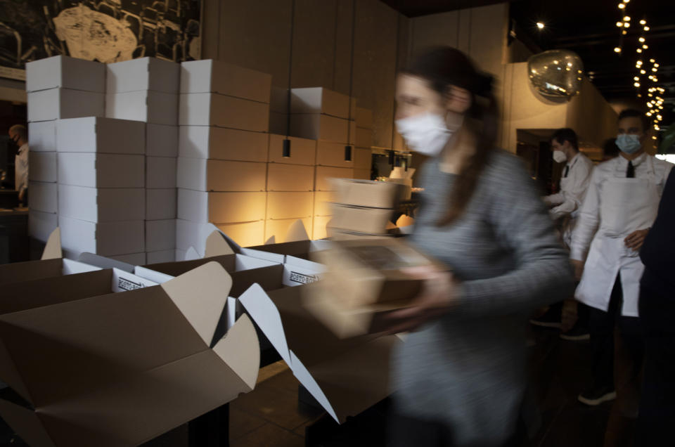 FILE - In this Saturday, Nov. 7, 2020 file photo, a restaurant staff member carries dinner boxes as she prepares part of nearly 600 take-away orders at Sergio Herman's Le Pristine restaurant in Antwerp, Belgium. The government on Monday, Feb. 22, 2021 presented scientific projections of the spread of the COVID-19 pandemic in Belgium, indicating it would be very risky to extensively loosen the current restrictions over the coming weeks. (AP Photo/Virginia Mayo, File)