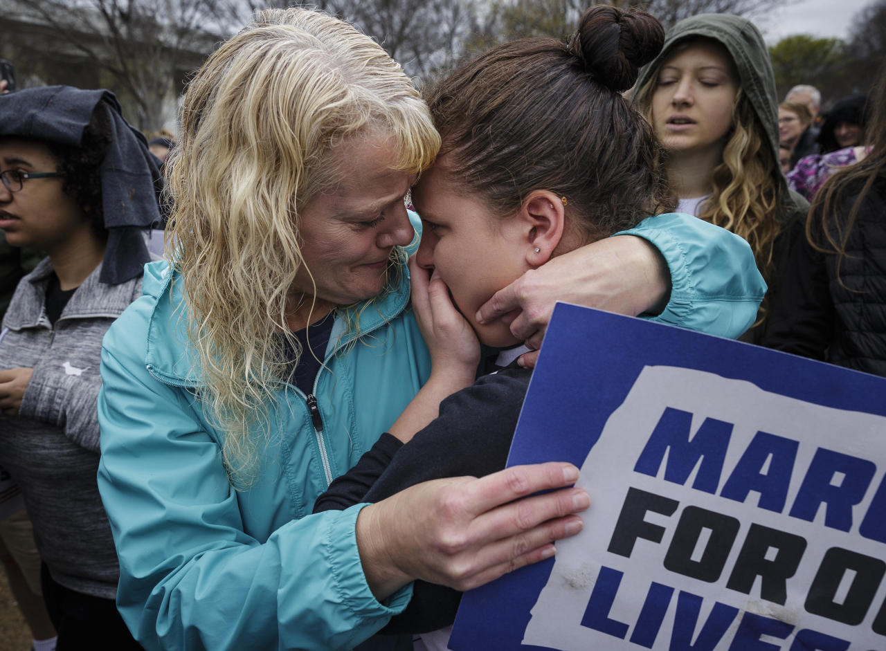 <p>Brenda Myers, center, comforts her daughter Jamie, who is an Ooltewah Middle School student, during an emotional moment after a moment of silence at the March for Our Lives in Coolidge Park on Saturday, March 24, 2018, in Chattanooga, Tenn. (Doug Strickland/Chattanooga Times Free Press via AP) </p>