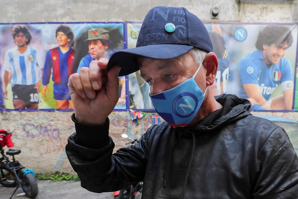 <p>A Napoli fan has wet eyes as he passes by portraits of Maradona at the popular 'Quartieri Spagnoli' in Naples</p>AP