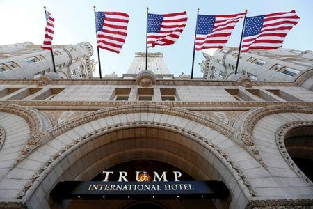 FILE PHOTO - Flags fly above the entrance to the new Trump International Hotel on its opening day in Washington