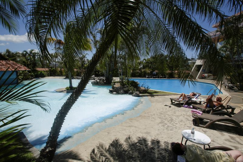 FILE PHOTO: Tourists sunbathe near a pool in a hotel, as Costa Rica tourism industry braces for coronavirus disease (COVID-19) outbreak, in Heredia