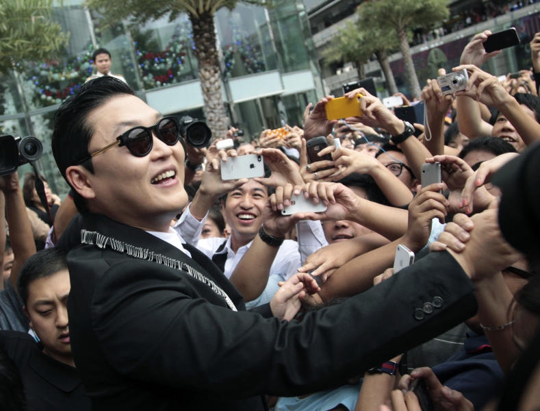 "FILE - In this Nov. 28, 2012 file photo, South Korean rapper PSY, who sings the popular ""Gangnam Style,"" greets Thai fans after a press conference in Bangkok, Thailand. As ""Gangnam Style"" gallops toward 1 billion views on YouTube, the first Asian pop artist to capture a massive global audience has gotten richer click by click. So too has his agent and his grandmother. But the money from music sales isn't flowing in from the rapper's homeland South Korea or elsewhere in Asia. With one song, 34-year-old Park Jae-sang — better known as PSY — is set to become a millionaire from YouTube ads and iTunes downloads, underlining a shift in how money is being made in the music business. (AP Photo/Sakchai Lalit, File)"